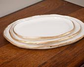 """Oval platters come in four sizes: Small - 9in. x 6.5in Medium - 10in. x 7.5"""" Large - 12in. x 9in. X Large - 14in. x 10in. Stoneware platters are handmade and hand painted with a glossy white glaze. The rim is accented with gold paint which is not food safe or dishwasher safe (just the gold rim is not food safe, but the white glaze is food safe). My recommendation is to use these platters for decorative purposes. Each piece is made to order with a lot of time and attention to deta..."""