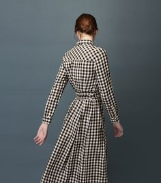 Pull-on shirt dress, with lightly pleated, tulip-shaped skirt, in a lovely and soft cotton double cloth - gingham on the outside, checked within. Short, neat collar. Long sleeves with buttoned cuff. Wide tie belt. Breast patch pocket and two side pockets.