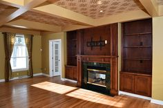 Living room with double-sided gas fireplace. Also includes wood built-in bookshelves and mantle. A coffered ceiling with recessed lighting and pattered wallpaper adds interest to the room.
