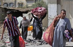 Palestinians carry belongings as they walk on the rubble of houses destroyed by Israeli strikes in Beit Hanoun, northern Gaza Strip, July 26, 2014. (AP Photo/Lefteris Pitarakis)