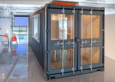 """""""Bare bones"""" office for tech startups that features a retrofitted shipping container and a wooden bleacher that doubles as a storage unit."""