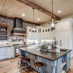 The rustic look continues through to the large farmhouse-style kitchen, which has wooden ceilings, exposed brick walls and shabby-chic cabinetry. A big kitchen island takes centre stage, and the bar stalls are reminiscent of those at a Wild West saloon. Farmhouse Style Kitchen, Shabby Chic Kitchen, Shabby Chic Homes, Kitchen Dining, Kitchen Decor, Kitchen Rustic, Kitchen Ideas, Modern Farmhouse, Country Chic Kitchen