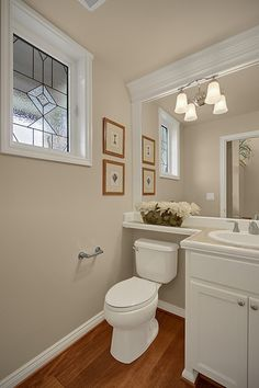 Traditional Powder Room with Inset cabinets, Limestone tile counters, Stained glass window, Powder room, Hardwood floors