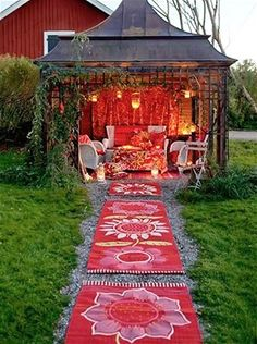 Bohemian chic ...this is so cool.. Bold flower-patterned rugs line the path to this bohemian backyard retreat. Hanging lanterns illuminate warm pink and red hues that contrast against clean white wicker pieces.