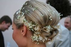 This beautiful bridal updo hairstyle would look lovely for an old fashioned wedding. The use of tiny babys breath flowers dot the hair that is intertwined with embroidered ribbon. Hair is pulled up and secured in a bun-like fashion at the back of the head. The ribbon is wound into the hair as it is twisted into place.  More on Delicate Bridal Updo