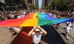 Alan Boyle helps carry a rainbow flag up Market Street during San Francisco's 43rd annual Gay Pride parade on Sunday, June 30, 2013. (AP Photo/Noah Berger)