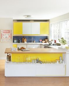 White Corian counters, plywood cabinets faced with yellow and white Formica, and cobalt penny tile backsplash in a New York kitchen.
