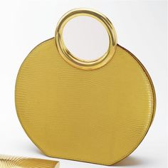 CARTIER GOLD AND YELLOW LIZARD HIDE HANDBAG, CARTIER, PARIS The circular handbag composed of yellow lizard hide completed by a gold handle, measuring approximately 8¾ by 2½ by 9½ inches, interior signed Cartier, Paris.