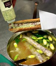 Actually it is a veau chaud (pronounced voh show) — literally hot veal — a slender nine-inch sausage made from edible bits of a cooked calf head, or tête de veau.    It is served with gribiche sauce (a vinaigrette with capers, cornichons, hard-boiled egg, herbs and mustard).