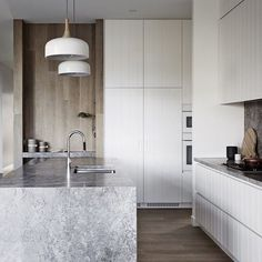 The white cabinetry with grey stone waterfall bench, set against the timber wall and floors comes together perfectly.