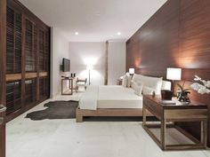Love how the wood accent wall and slatted wood closet parallel each other in this minimalist bedroom.