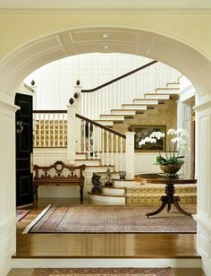 This entryway has so much going for it - archway, furniture, stairway