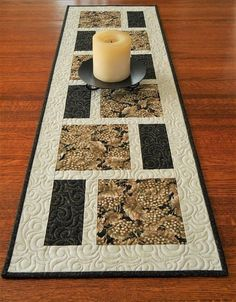This wine-themed quilted table runner features glistening grapes on the vine in taupe and ivory on a black background. The fabric used for the smaller blocks is black with tiny brown leaves, and the background is ivory with a subtle linen look. This would be perfect for a wine tasting party, but could also be used as part of your everyday decor. The size is approximately 13-1/2 X 44 (34 X 112 cm) - a versatile size for use on a dining table, buffet, or coffee table. I machine-quilted al...