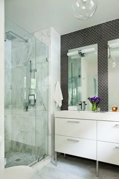 Small subway tile, larger vanity drawers, light fixture mounted on mirror