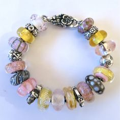 "CLOCKWISE FROM CLASP:  ""CHERRY BLOSSOM CLASP"", ""UNIQUE"", ""SEVEN CHAKRAS"", ""UNIQUE AMBER"", ""ENGRAVED ROMANCE"", ""THE POSITIVE NO"", ""PINK GOLD"", ""TROPICAL CONCH"", ""DESERT ROSE"", ""COMPASS"", ""HONEY DAWN"", ""ROSE QUARTZ"", ""SILVER TRACE, GOLD"", ""WILD CHERRY"", ""PINK PETALS"", ""NEPTUNE'S PROMISE"", ""DESERT ROSE"", ""GUARDIAN OF NATURE"", ""PINK CONCH"", ""UNIQUE AMBER"", ""SEVEN CHAKRAS"", ""UNIQUE""."