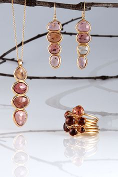 I love to mix the shades of tourmalines.    Rose cut tourmaline slice totem pendant and earrings and custom-cut cabochon blossom stacking rings. All set in 14k yellow gold.