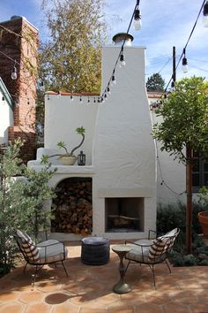 The exterior patio conjures an Italian piazza with bistro lights strung overhead, and a pair of modern steel frame chairs flank an outdoor fireplace.