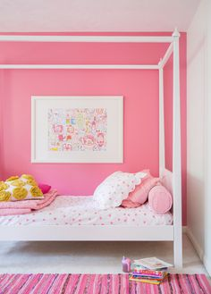 Beautiful pink bedroom interior design for girls bedroom featuring a lovely deep pink shade feature wall with a rug and details on the bedding of the same hues, contrasted by white painted four poster bed, white walls and ceiling and white carpets. Modern chic bedroom for little girls who love pink! Photo credit: Brittany Ambridge, Domino…