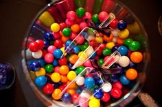 A colorful assortment of gumballs in a large martini glass with his and her scoops!  Just one of the many ideas for added fun and flavor to your candy bar!