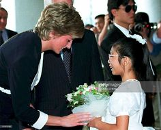 Princess Diana receives flowers from Stella Chan, a daughter of a cancer patient, during a tour of a local hospital 22 April in Hong Kong. The Princess of Wales is on a three-day working visit to the territory.