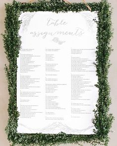www.verbenafloral.com -Guests found their seats for the buffet-style dinner on a sign framed with boxwood greenery by Verbena Floral Design