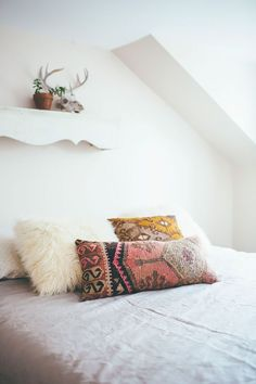 Light, airy, boho bedroom with gorgeous pillows and textiles