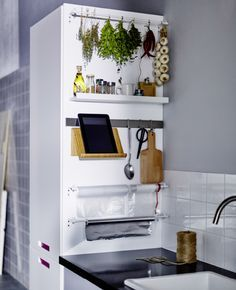 El lateral de un armario alto de cocina con cestas y raíles para un punto de almacenaje