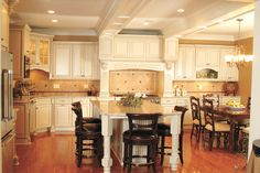 Traditional white kitchen cabinets with wood hood, crown molding and decorative legs.