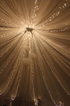 Painters plastic and Christmas lights tied to a metal ring then roped up to the ceiling, draped over wire at the edges... Indoor Tent! :) :)