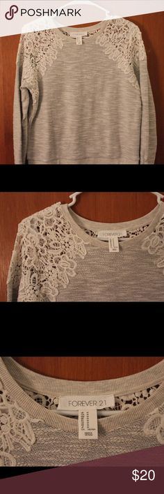 Forever 21 gray sweater with lace Forever 21 gray sweater with white lace on the shoulder and the top of the back. Haven't worn before Forever 21 Tops Blouses