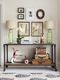 Industrial entry table || framed pressed flowers || green glass lamps || stacked vintage luggage