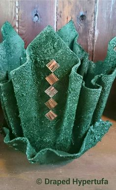 A green painted medium sized Draped Hypertufa Planter. It is decorated with tiles.