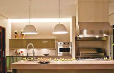 """Para imprimir uma atmosfera acolhedora a esta cozinha gourmet apostou-se em níveis luminosos contrastantes. """"É o oposto de uma luz uniforme"""". Na parede ao fundo, a sanca de gesso embute fluorescentes de 32 w. Fixadas na parte inferior dos armários, halógenas bipino de 20 w driblam a perda de luminosidade na área de trabalho. Chamativos, os dois pendentes de alumínio (Ômega Light) mais do que pontuam o balcão. """"Eles a ajudam a disfarçar a presença da coifa industrial."""