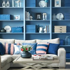 Coastal living room with blue walls, blue shelving, neutral sofa and striped red and blue cushions