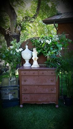 vintage dresser and trunks, cement, and greenery.
