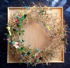 Hangend object: van stokjes een frame / krans gemaakt. Waarop bloemen zijn bevestigd.  Is David 花藝 /Flower Studio, Taiwan