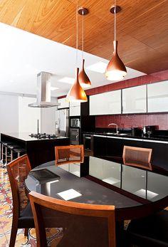 Decoração de casa com materiais nobres e acabamentos sofisticados na cozinha banqueta preta, armário cinza, revestimento vermelho, pendentes, mesa de jantar de madeira com tampo de vidro.