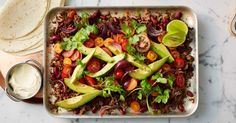 Served with fresh avocado, sour cream and tortillas, this spicy one-pan tray bake will easily feed a crowd.