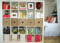shelving-as-room-divider-ideas; use decorative bins for storage and visual separation; good idea to partially  separate playroom (previously formal living room) space from formal dining room