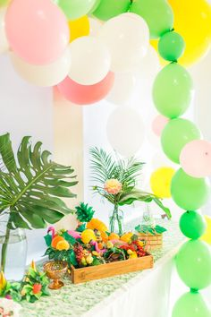 Party table with palm fronds and balloon arch from a Tropical FOURest Birthday Party at Kara's Party Ideas