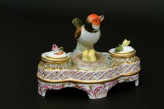 """Herend Porcelain Inkwell - The lobed form with pierced basket weave gallery, two inkwells with rose finials, surmounted by a songbird nesting with her chicks, hand-painted in polychrome enamels and gilt. 4 1/2""""H. 6""""W. 4 1/2""""D. Condition: two tiny flakes to pink rose finial."""