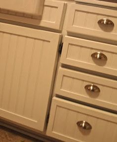 Kitchen cabinet rehab with beadboard + trim pieces + paint.  Great idea if you have horrible cabinet doors.