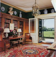Foyer doubling as a library - rug, table with two lamps, leather chairs, heavy mouldings on bookshelves, lantern, blue and white porcelain - Architectural Digest