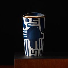 A double-walled travel mug featuring a geometric pattern with navy and gold accents.