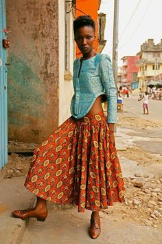 The yoke of the skirt resting low on her hips, the luxuriously gathered skirt, wildly tailored jacket, her sultry stance and the squalor behind her.  I don't know what the Maleombho Collection is, but I know a great photograph when I see it. Nina.