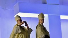 A bishop takes snapshots before the start of the World Youth Day (WYD) opening mass, at Copacabana beach in Rio de Janeiro, Brazil