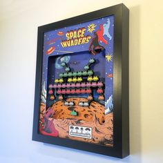 "Its a Space Invaders shadow box! Arcade style pixel graphics!  The art is made from meticulously cut prints and foamboard, and shows invading hordes of aliens, descending in the formation of a huge alien. There are multiple tiers for a deep 3D effect that really pops. It looks more ""poppy"" once you get it in your hands.  The frame is 8 x 10, and is included. (The glass has been removed for the photos, but yours will have glass).  -Made of layered foam board -Solid MDF frame -Best gift of…"