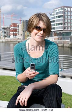 A young woman at Marco Polo Terrassen in the new built Harbourcity/Hafencity in Hamburg, Germany sending a text message with her - Stockbild