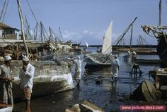 Fishermen stand beside boats aground in harbor at low tide. Zanzibar Island. (Date: 1/2/1952)