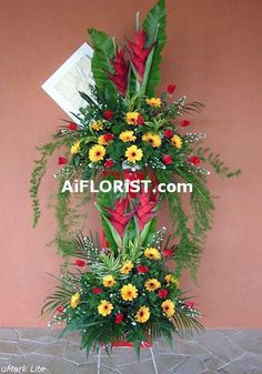 A grand arrangement of two tier stand of Tropical Heliconia, Roses & Red Gerberas perfectly for any official openings